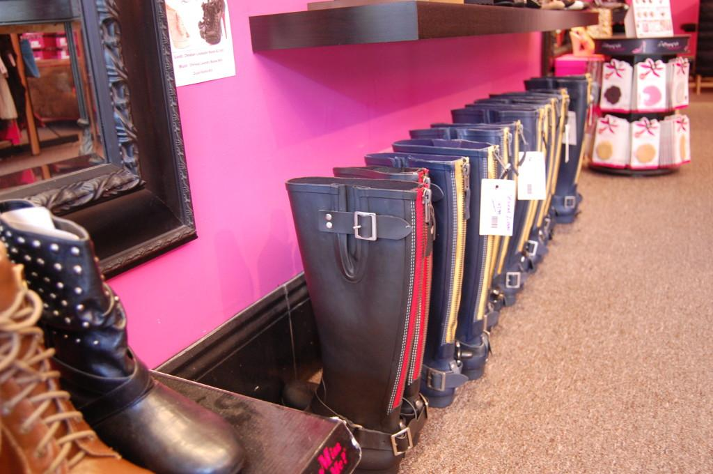A row of multi-colored rain boots line one wall.