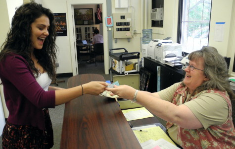 Community High School junior Carly Paull-Baird buys her prom ticket in the main office from Chris Hicks.