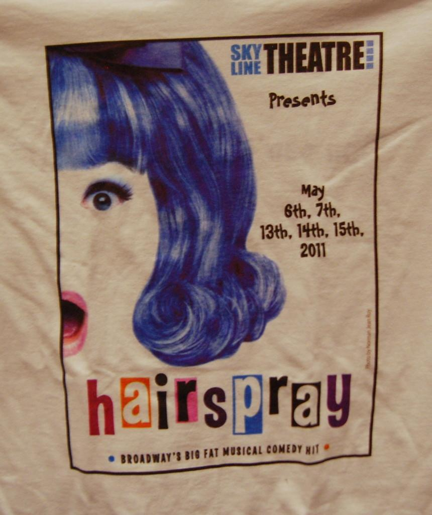 The t-shirt of an audience member advertising Skylines Hairspray.