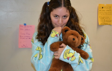 Julia Devarti, dressed as a baby, holds her teddy bear and sucks her thumb.