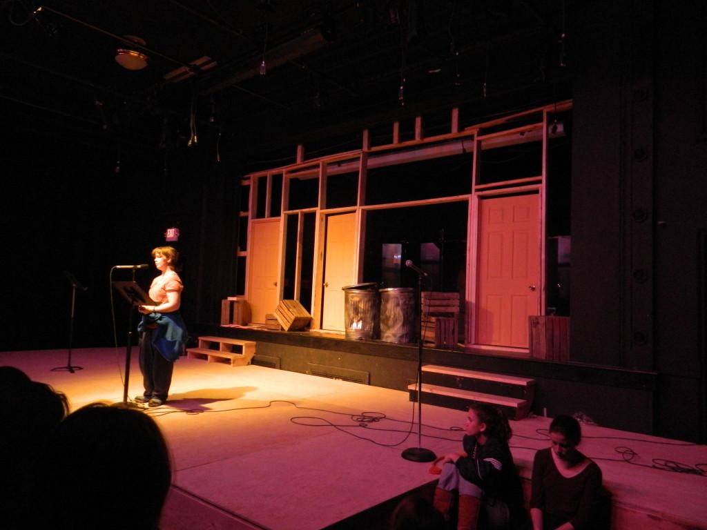 CHS senior Jess Maronen reads in the second round of the poetry slam. The performers stood in front of the set design for CETs upcoming production of Avenue Q.