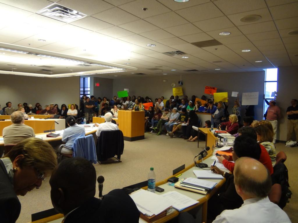 Proponents+of+the+Clemente+program+speak+to+school+board+members+as+other+hold+up+signs+in+the+background.