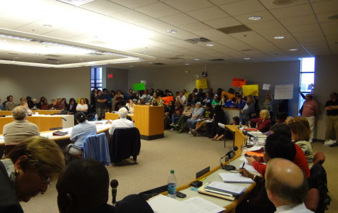 Proponents of the Clemente program speak to school board members as other hold up signs in the background.