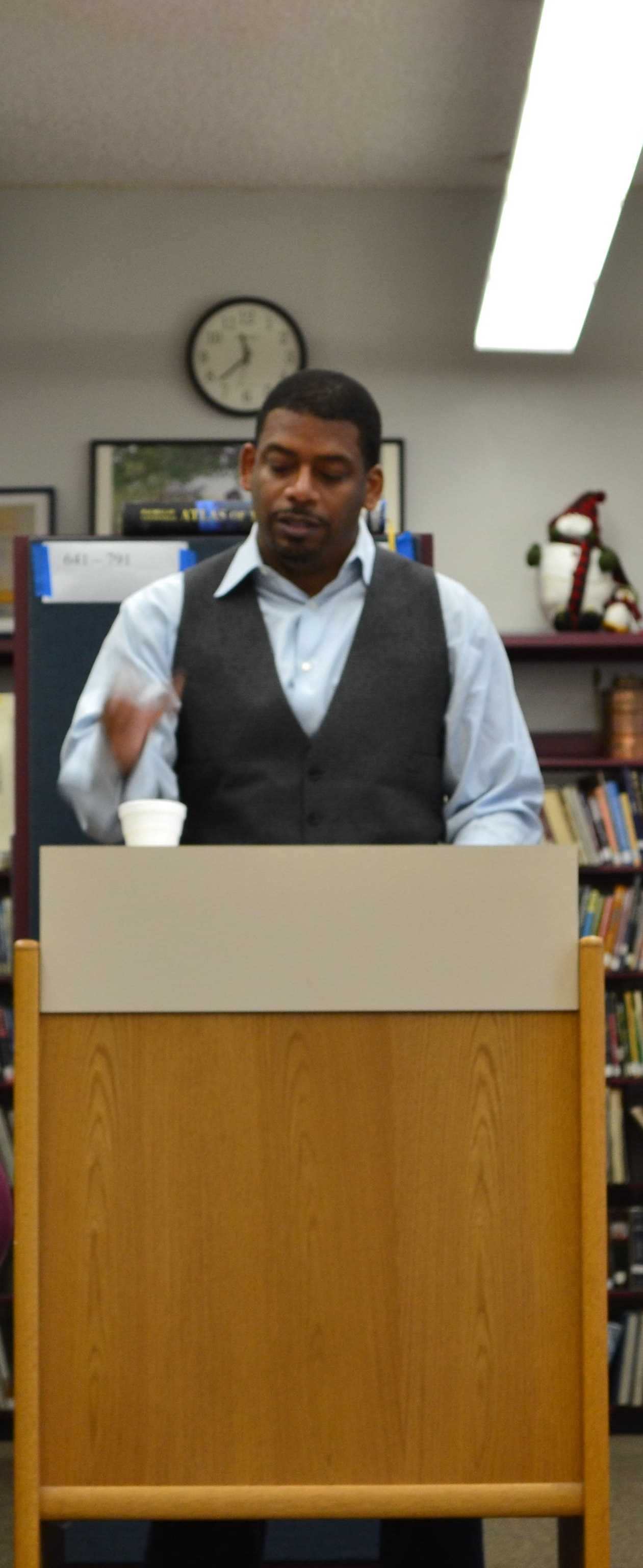 A. Van Jordan reading his poetry in the media center.