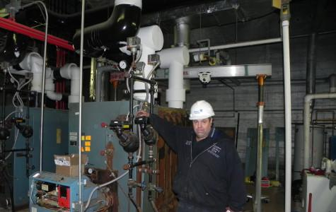 Andrew Bronson, employed by Johnson Controls, poses with one of the boilers.