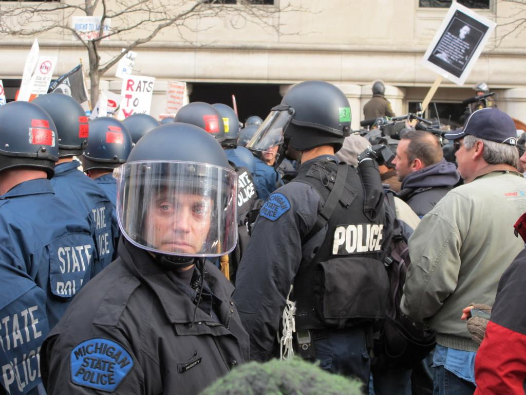 An+officer+scans+the+crowd+as+the+line+of+police+that+attempted+to+clear+the+street+is+surrounded.+From+here+they+moved+to+the+front+of+the+George+W.+Romney+building%2C+preventing+protestors+from+entering.