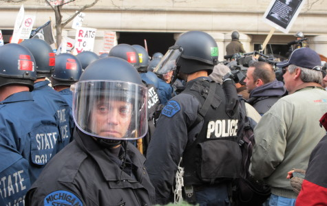 An officer scans the crowd as the line of police that attempted to clear the street is surrounded. From here they moved to the front of the George W. Romney building, preventing protestors from entering.