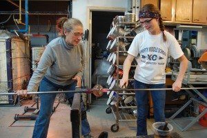 Annette Baron (left) and Raquel Goosey (right) use a punty to transfer a piece.