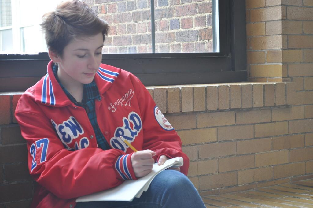 Alice Held writing poetry on the third floor of CHS.