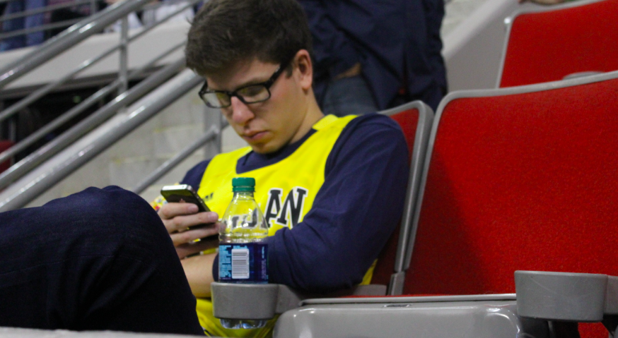 Lounging in a chair outside of a VIP suite this Michigan fan is too distracted by technology to enjoy the game.