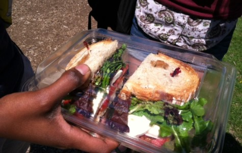Senior Leah Awkward-Rich holds out a mozzarella, tomato, and lettuce sandwich purchased from Sparrow for $4.