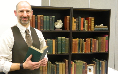 David Wooten stands with selections from his antique book collection. The collection centers around works that inspired naturalist Charles Darwin.