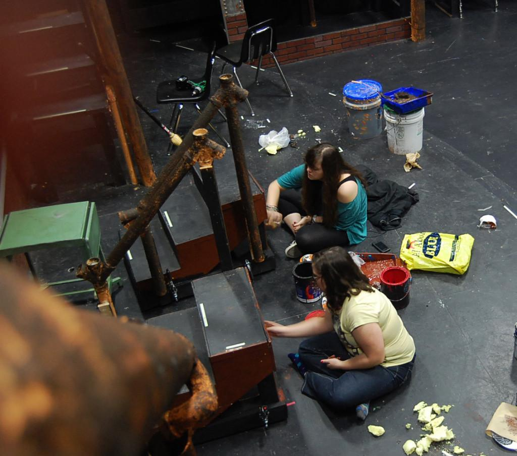 Briana O'Neal and Alexandra Cubero-Matos paint the Urinetown set the morning of the show