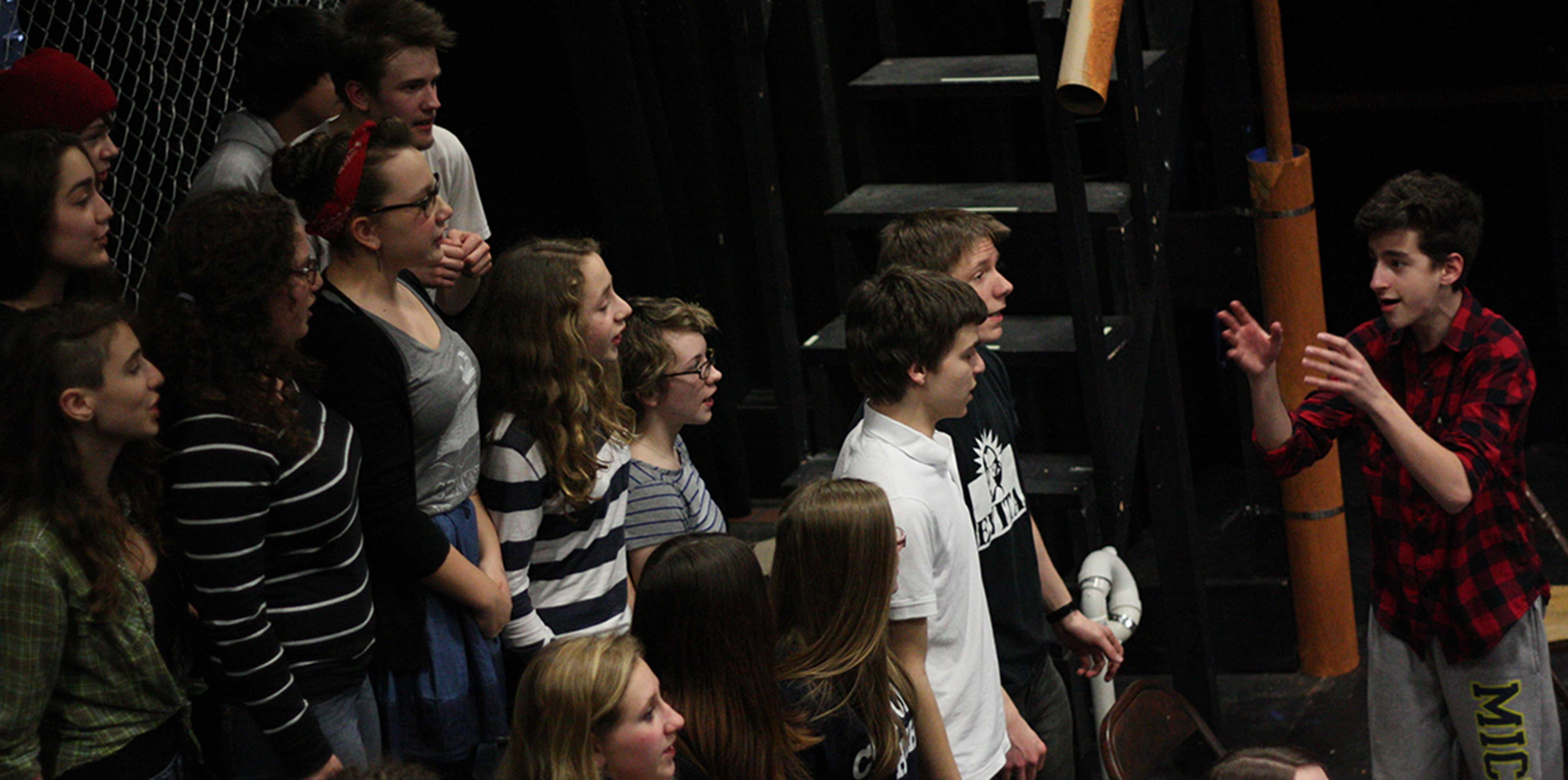 Actors, led by Isaac Scobey-Thal as Bobby Strong, rehearse the song