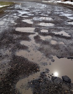 Potholes covering the entry-road to the Meadowins subdivision