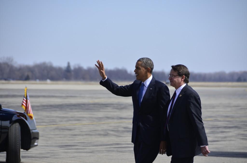 The President waves as he walks toward the motorcade.