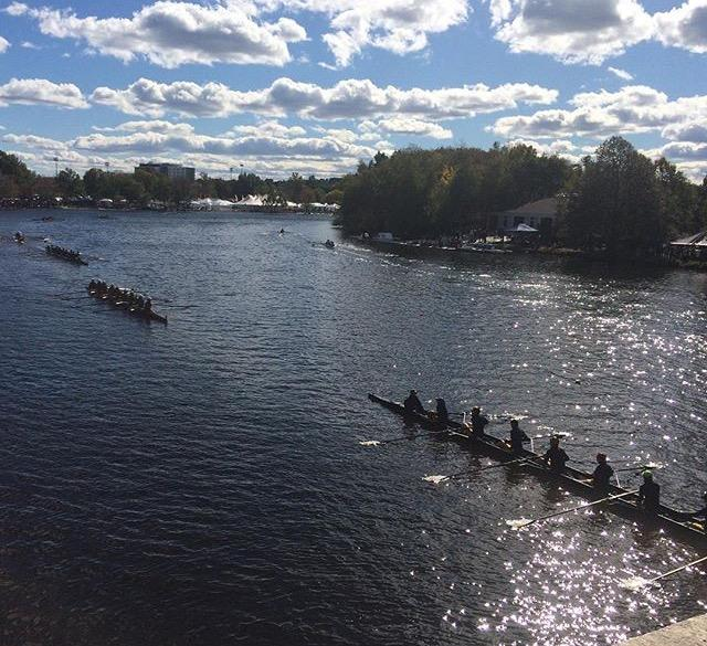 Boats are racing and rowing up to the start on the Charles River going under Eliot bridge, which is one of the most difficult turns of the race.