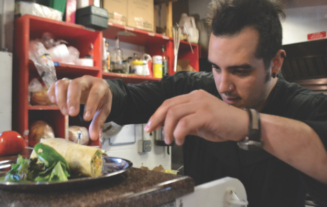Gregorio DiMarco displays his gregarious personality while putting the finishing touches on the Breakfast Burrito in Sparrow market's kitchen.