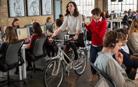 Jules Ostin (Anne Hathaway) rides her bike from meeting to meeting through her office to save time.