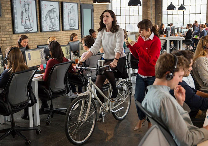 Jules+Ostin+%28Anne+Hathaway%29+rides+her+bike+from+meeting+to+meeting+through+her+office+to+save+time.