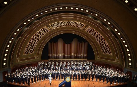 The Michigan Marching Band plays on Hill Auditorium as the Drum Major, Matt Cloutier, directs in front.