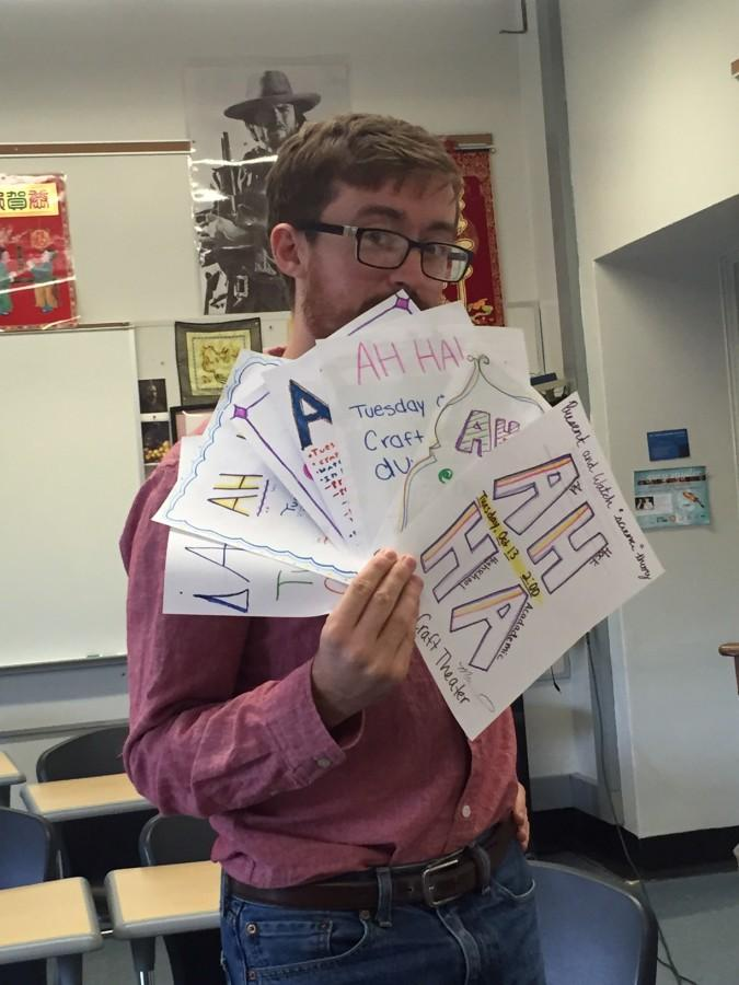 Robert Morgan holds posters his creative writing students created to advertise for the Ah Ha! Fest.