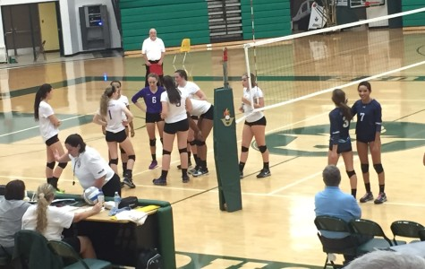 Pioneer's team huddles during a game delay while Ella Eliason (3) and Chandra Jackson (4) wait for permission from the referee to subtitute.