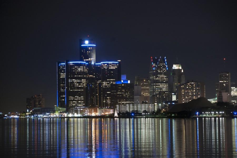 The city of Detroit reflects onto the Detroit River.