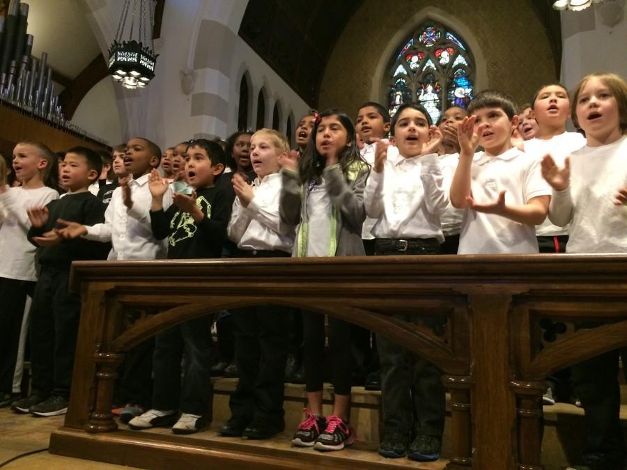 Dicken students singing with coordinated hand gestures.