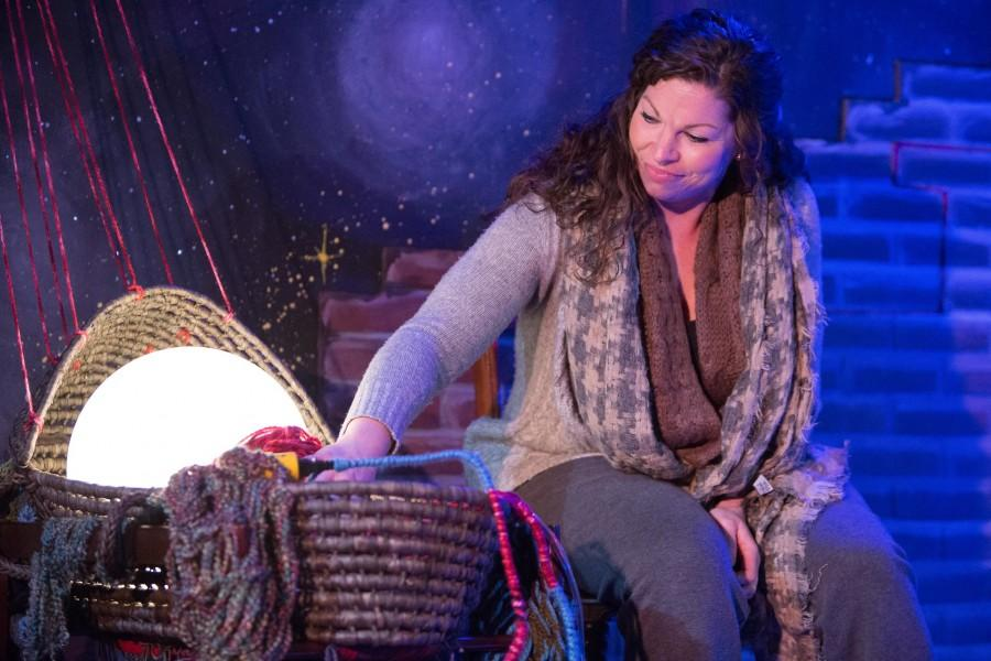 Actress Vanessa Swanson as her character Natalia in Kickshaw Theaters production of The Electric Baby. Swanson comforts her magical baby with stories and songs of her homeland of Romania.