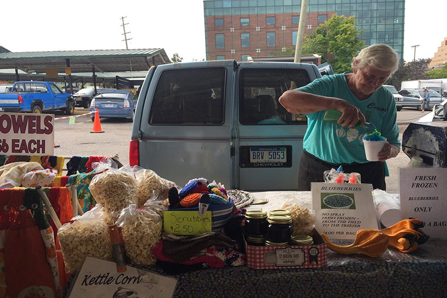 Carol Brooks making her customers a snow cone on Wednesday at the Ann Arbor Farmers Market.