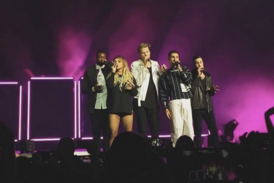 Pentatonix (Kevin Olusola, Kirstie Maldonado, Scott Hoying, Mitch Grassi and Avi Kaplan) at the front of the stage during one of their songs.