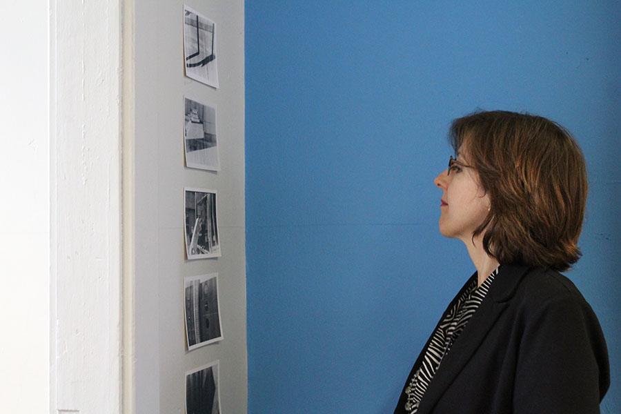 Assistant Dean Karen Siegal admiring photographs from Steve Coron's film photography class.