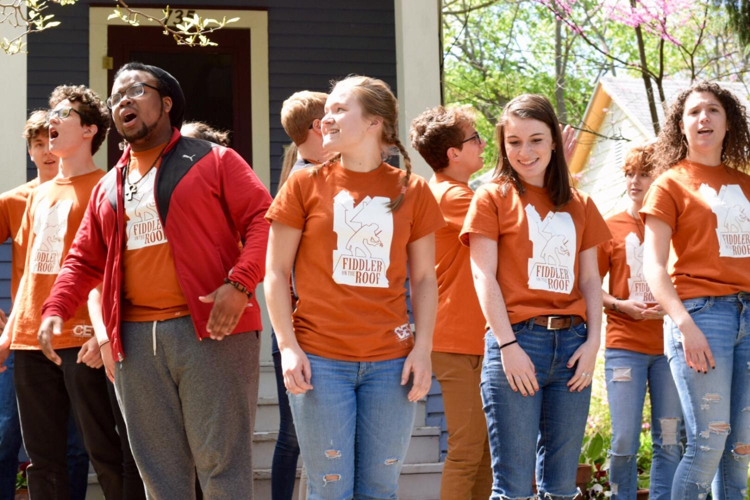 Clarence Collins III, Ellen Reed, Isabel Ratner, and others dance and sing sporting orange t-shirts from the show.