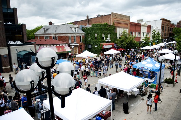 A photo of main street from above, with lines of people waiting to get food at the white tents.