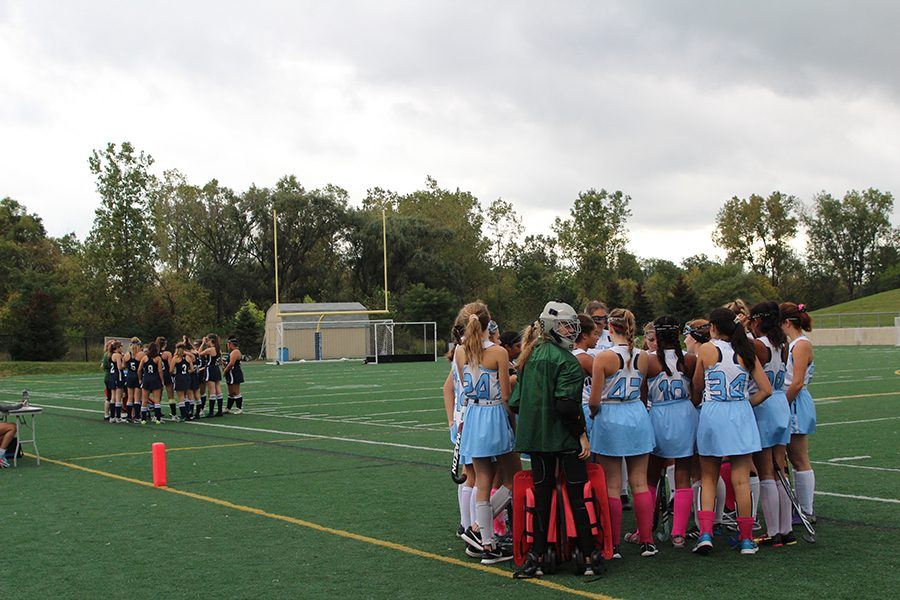 JV teams from Ann Arbor Skyline and Cranbrook-Kingswood huddle before the start of the game.