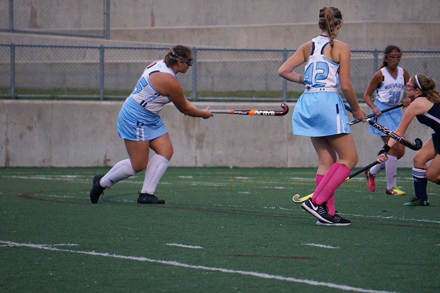 Isabel Espinosa watches just after hitting the ball as Julia Barge tips it into the goal during a penalty corner.