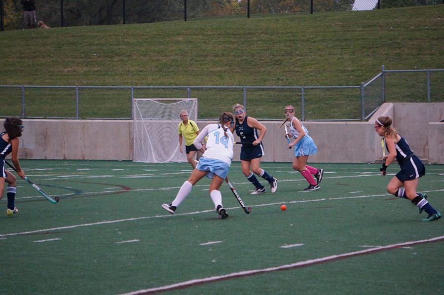 Sophomore Captain Sydney Vigo carries the ball up the field towards the goal as Cranbrook's defense prepares for the shot.