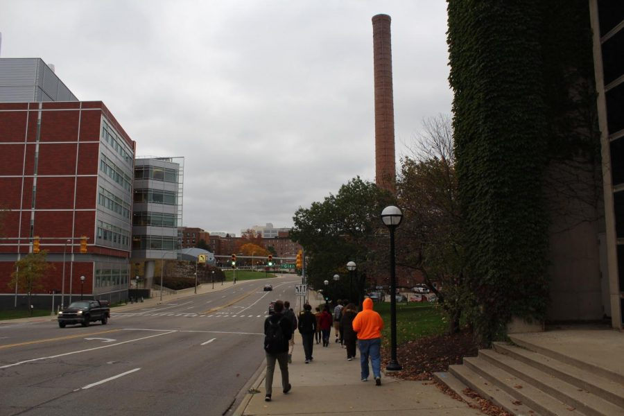 Group of engineering and physics students walk down to the power plant. When the power plant was originally built it was at the lowest point on campus, so condensed steam could come back to the plant and be reused.