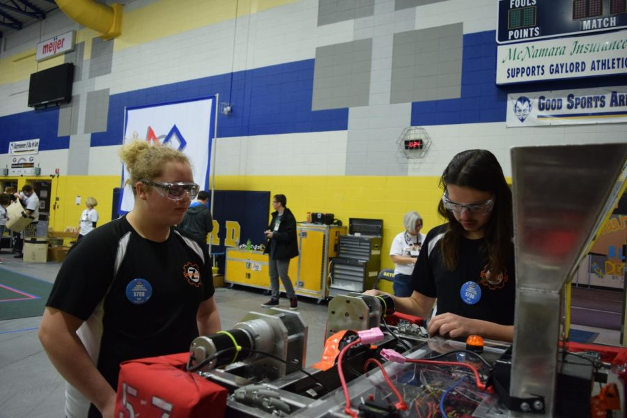 Senior Zenna Hodges and sophomore Cort Toschlog-Green make final preparations before a match at competition in Gaylord, Michigan. Before a match, the team must make sure the foam bumpers on their robot are switched to the right color—either red or blue—to correspond to their alliance for that round.