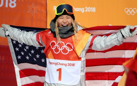 Chloe KIm celebrates with the USA flag in the women's halfpipe at the 2018 Winter Olympics.