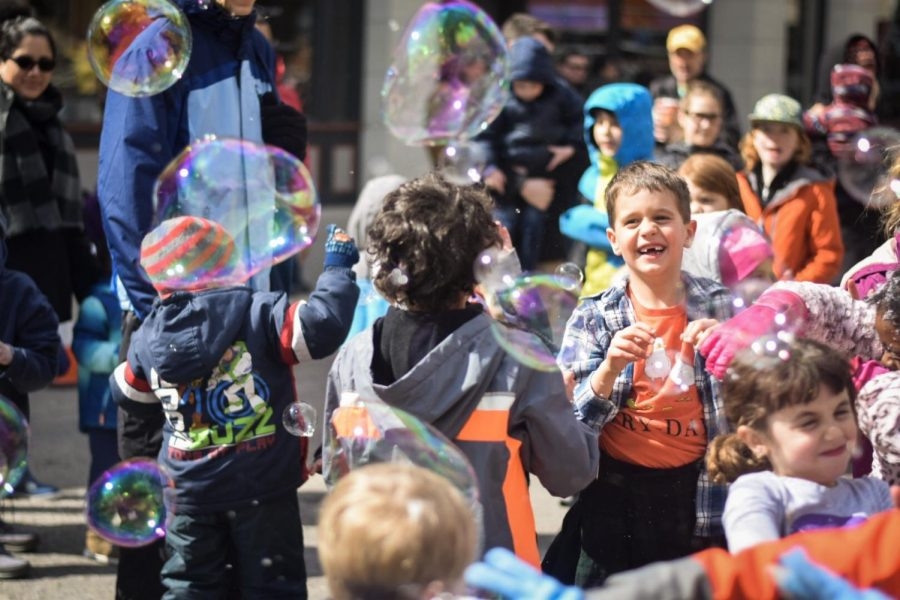 Kids play with bubbles in the middle of Main St. before the parade begins.