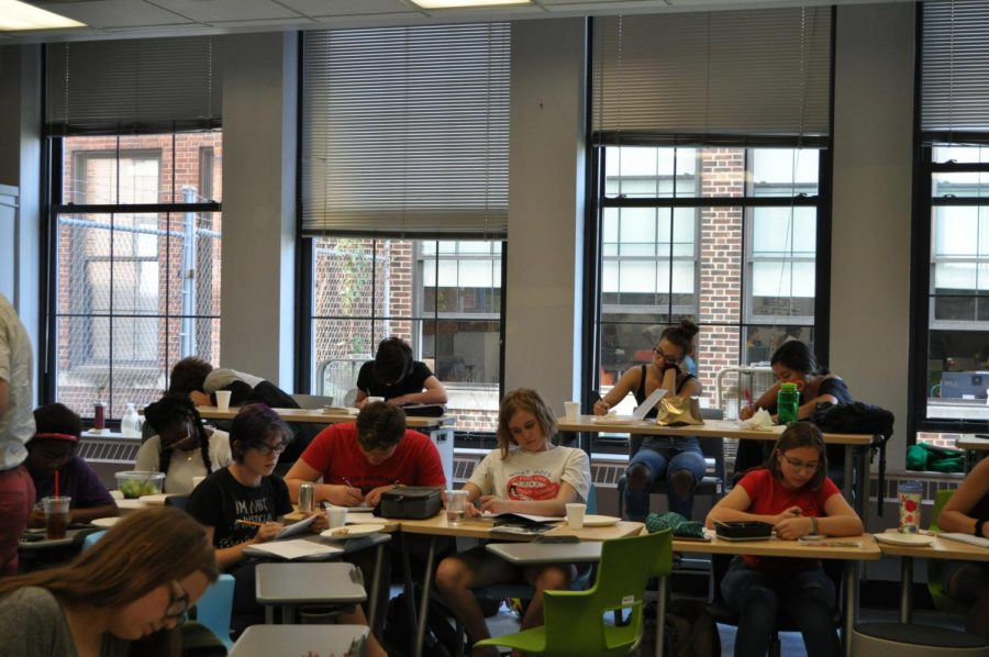 Poetry club members spend a moment of quietly writing. The club includes opportunities to both read and write poetry.