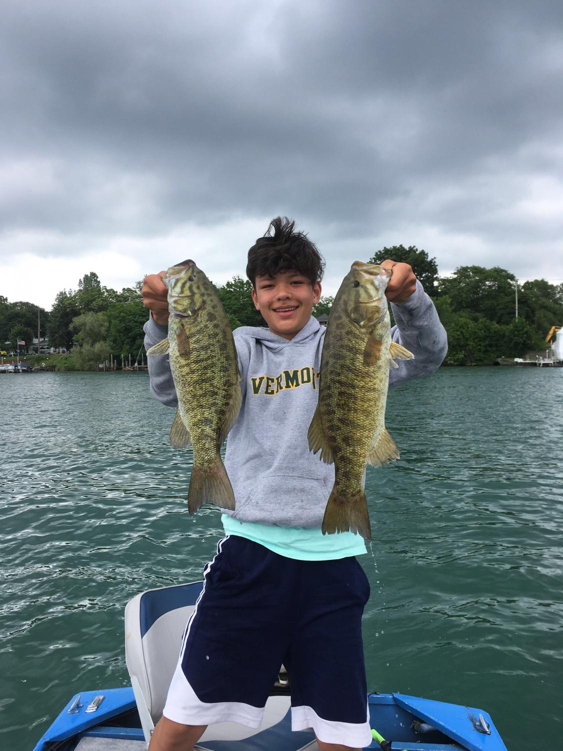 Tang+displaying+his+two+best+catches+before+getting+off+of+the+Detroit+River+after+a+successful+day+on+the+water.