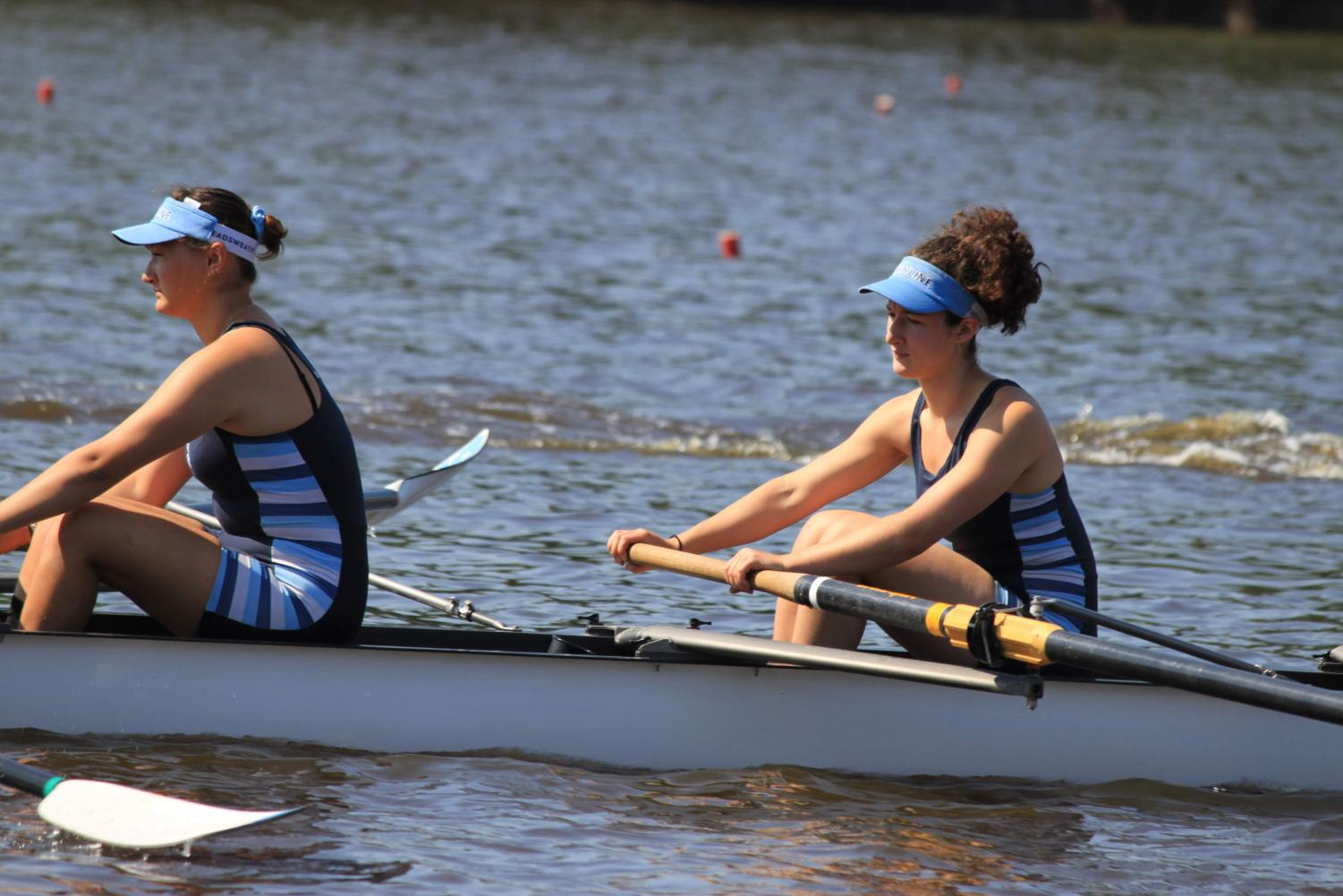 Mira Simonton-Chao and Ella Edelstein rowing, clad in their 'columbia-blue' Skyline crew uniforms. They were both a part of the freshman four-person team that won at the National Championships.