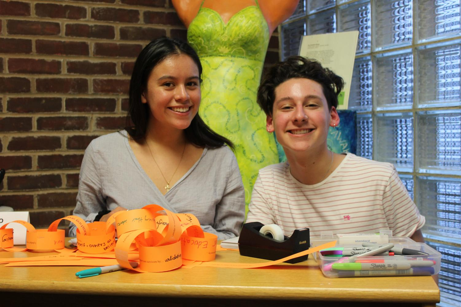 Two Teen Voice peers sit at a welcome table with orange slips of paper prompting guests to think about ways to help survivors.