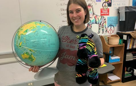 New social studies teacher Sarah Hechler holds up a globe and a rainbow zebra, two essential decor items in her classroom.