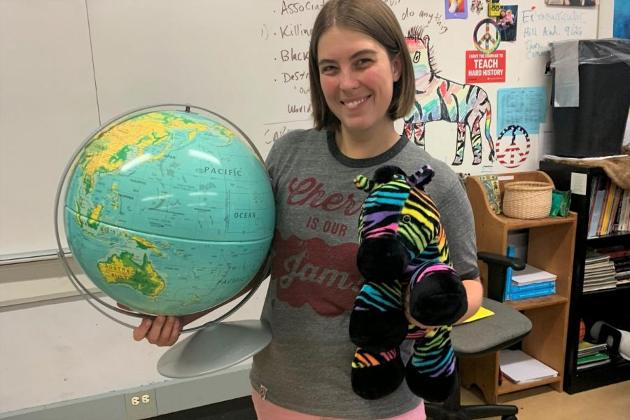 New+social+studies+teacher+Sarah+Hechler+holds+up+a+globe+and+a+rainbow+zebra%2C+two+essential+decor+items+in+her+classroom.