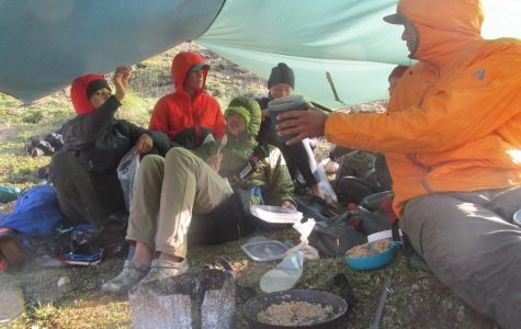 My course group enjoying oatmeal under a kitchen tarp in the Talkeetna Mountain Range in Alaska.
