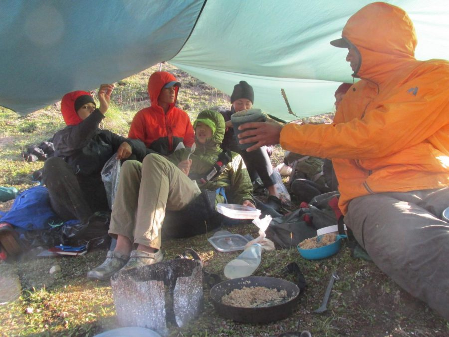 My+course+group+enjoying+oatmeal+under+a+kitchen+tarp+in+the+Talkeetna+Mountain+Range+in+Alaska.
